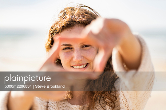 Happy young woman with red hair forming a frame with her hands, Portugal - p300m2286834 von Steve Brookland