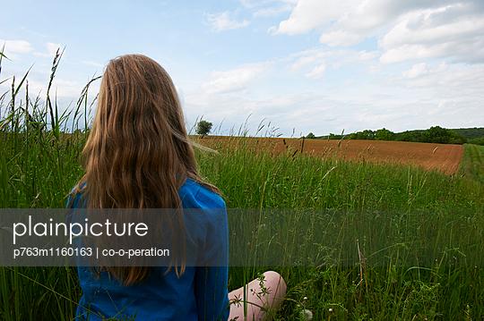 Mädchen sitzt auf einer Wiese - p763m1160163 von co-o-peration