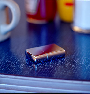 Lighter on table top - p1082m2228221 by Daniel Allan