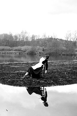 Reflection, Maid sitting on a chair next to lake - p1521m2158319 by Charlotte Zobel