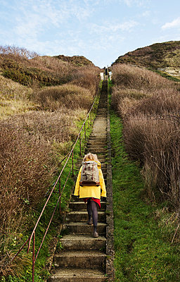 Girl with retro backpack moving up stairway near former NATO fuel station on Normandy coast - p429m1557426 by Mischa Keijser