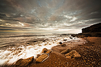Water washing up on the shore along the coastline under a cloudy sky - p442m884035f by John Short