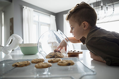 Boy reaching into cookie jar in kitchen - p1192m1231349 by Hero Images
