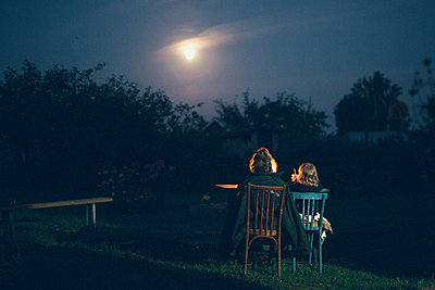 Two girls in the garden at night looking at the moon - p1642m2222221 by V-fokuse