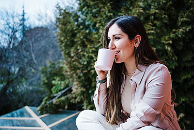Woman drinking coffee while sitting on balcony - p300m2274581 by Eva Blanco