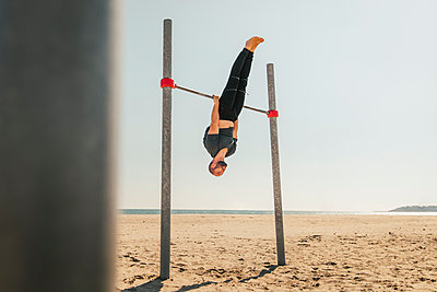 Male athlete practicing on high bar at beach - p300m2281318 by Aitor Carrera Porté
