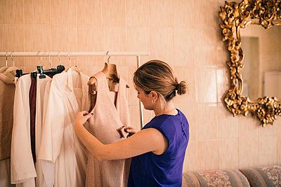 Female fashion designer examining dress on rack at workshop - p300m2293502 by LUPE RODRIGUEZ