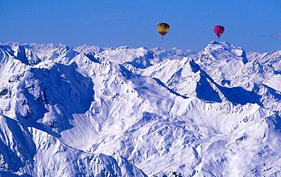 Hot air balloon flying over the snowy peaks at Austria - p34811475 by Claes AxstAl