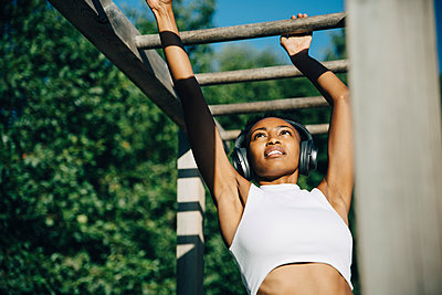 Sportswoman listening music through headphones while exercising on monkey bar in park - p426m2270819 by Maskot