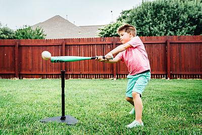 Caucasian boy hitting baseball off tee in backyard - p555m1304495 by Inti St Clair photography