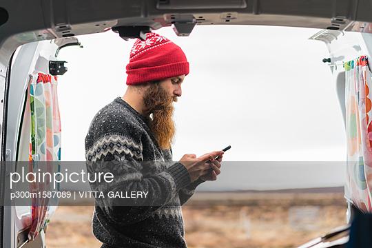 Hipster standing at van using cell phone - p300m1587089 von VITTA GALLERY