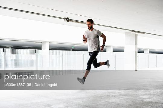 Man running in parking garage - p300m1587138 von Daniel Ingold