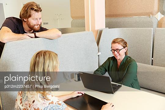 Coworkers talking at work - p312m2237457 by Phia Bergdahl