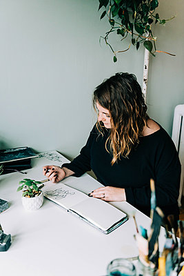 Stock photo of a lettering artist at work with her sketch book. - p1166m2162666 by Cavan Images