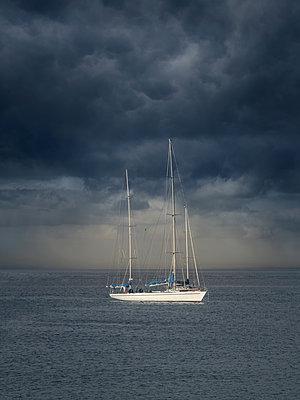 Weiße Segelyacht unter dunklen Wolken - p1280m2126811 von Dave Wall