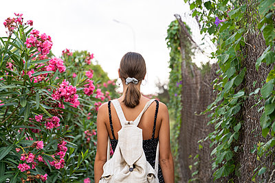 Back view of young woman with backpack strolling in a park - p300m2143349 von VITTA GALLERY