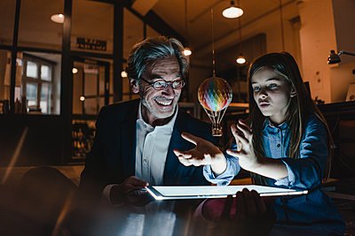 Happy senior buisinessman and girl with hot-air balloon and shining tablet in office - p300m2155282 by Gustafsson