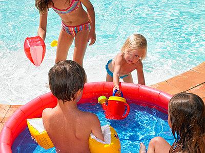 Four children playing in a kiddie pool near a backyard pool. - p4291509f by Ghislain & Marie David de Lossy