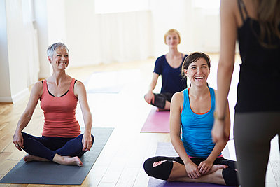 Female students watching and listening to tutor in pilates class - p429m983243f by Liam Norris