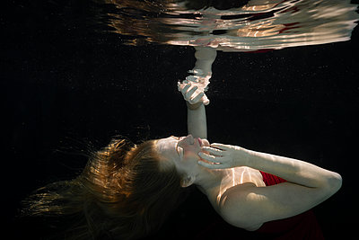 Woman in red dress under water - p1554m2272601 by Tina Gutierrez
