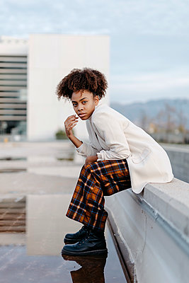 Young woman with afro hair sitting on retaining wall over puddle against building - p300m2256650 by Tania Cervián