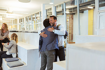 Smiling businessman embracing male colleague while standing in office - p426m2087912 by Kentaroo Tryman