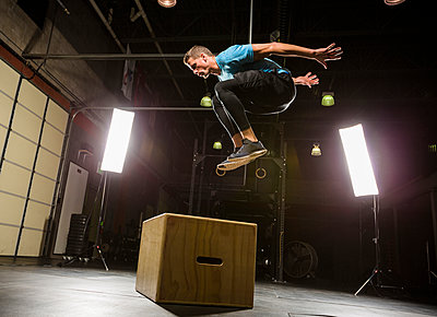 Caucasian man jumping on box in gymnasium - p555m1303450 by Mike Kemp