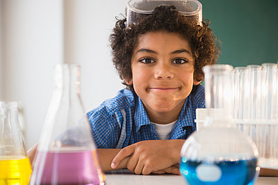 Mixed race boy sitting in classroom science lab - p555m1421111 by JGI/Jamie Grill