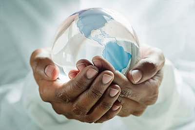 Mixed race man holding glass globe - p555m1478184 by REB Images