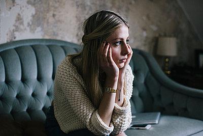 Blonde Frau sitzt bekümmert auf dem Sofa - p586m953904 von Kniel Synnatzschke