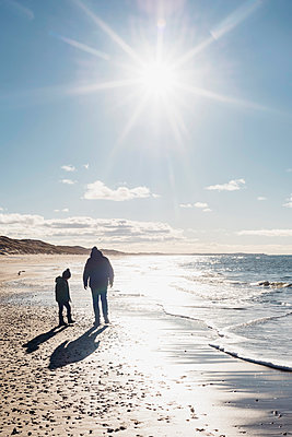 Denmark, Hirtshals, father and son walking on beach in backlight - p300m1189482 by Jana Mänz