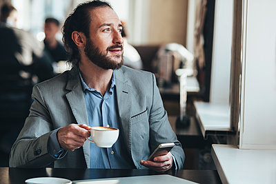 Mid adult businessman holding coffee cup and mobile phone in cafe - p301m1101882f by Vasily Pindyurin