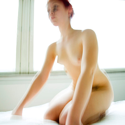 Young woman on bed - p4130001 by Tuomas Marttila