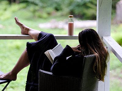 Frau auf der Veranda liest ein Buch - p551m2134365 von Kai Peters