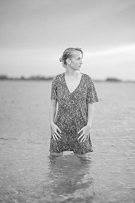 Junge Frau steht im Wasser - p552m2194526 von Leander Hopf