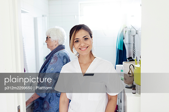 Smiling nurse looking at camera, elderly woman in background - p312m2299650 by Plattform