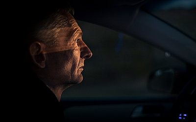Mature man travels by car at night - p1324m1165161 by Michael Hopf
