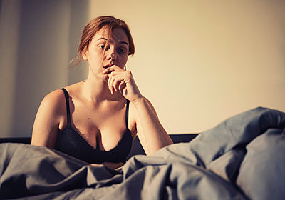 Woman in underwear with hand to chin in bed - p1569m2195806 by Moritz Metzger