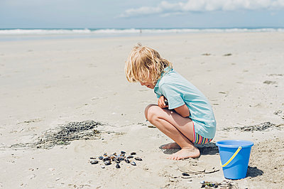 France, Brittany, Finistere, Pointe de la Torche, boy playing with seashells on the beach - p300m1120557f by Jana Mänz