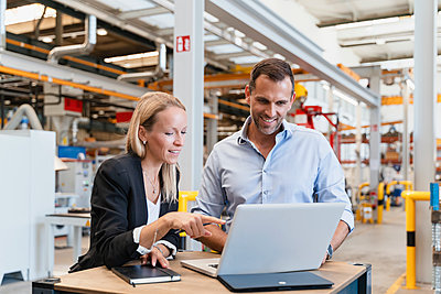 Smiling businessman and female entrepreneur using laptop at factory - p300m2240127 by Daniel Ingold