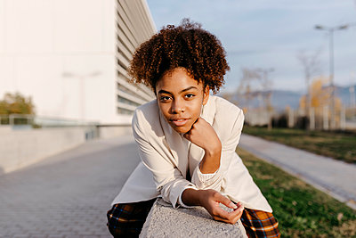 Confident young woman with afro hair sitting on retaining wall in city - p300m2257319 by Tania Cervián