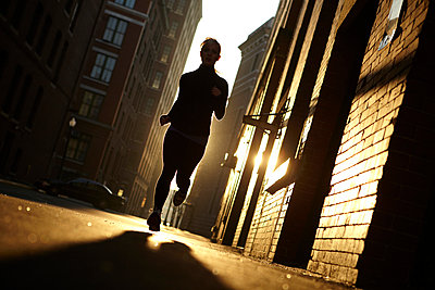 A female athlete running (Back Lit) - p343m1090247 by Josh Campbell