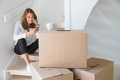 Woman sitting on staircase with smart phone and cardboard boxes - p352m2119091 by Helena Bonnevier