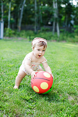 Barefoot female toddler picking up spotty ball in garden - p924m1404196 by Sasha Gulish