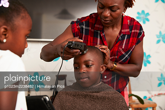 Mother with trimmers cutting son hair in bathroom - p1023m2238482 by Himalayan Pics