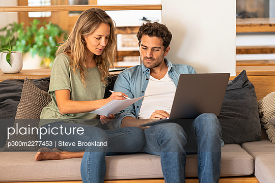 Girlfriend signing papers by man with laptop sitting on couch at home - p300m2277453 by Steve Brookland