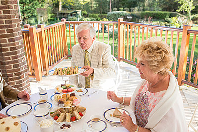 Senior people having tea on the balcony - p1026m1164204 by Patrick Frost