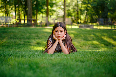 A tween girl lays in the grass with her head propped in her hands - p1166m2213130 by Cavan Images