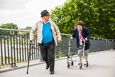 Senior couple with walking stick and wheeled walker - p300m1047403f by Uwe Umstätter
