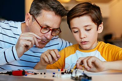 Father and son assembling an electronic construction kit - p300m1562510 by Bonninstudio